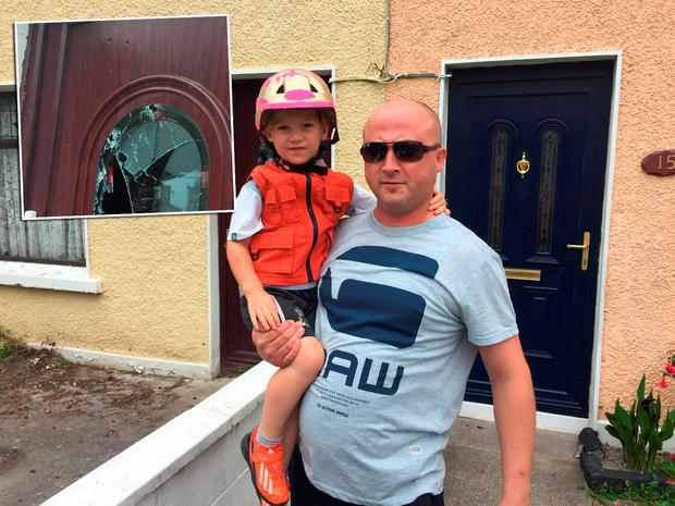 Lubos Kocik with son Gordon (3) on Cuala Road. Inset: Visible bullet holes on the door in Cabra