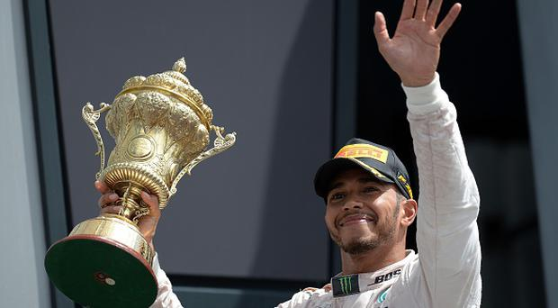 Mercedes AMG Petronas F1 Team's British driver Lewis Hamilton lifts the trophy as he celebrates on the podium after the British Formula One Grand Prix at Silverstone motor racing circuit in Silverstone, central England, on July 10, 2016. Lewis Hamilton streaked away to comfortably win his home British Grand Prix on Sunday, with Mercedes team-mate Nico Rosberg hanging on for a provisional second. Third was the Red Bull of Max Verstappen, but championship leader Rosberg -- suffering late gear-box trouble -- was under investigation over a radio communication that could spell further trouble for the German. / AFP / OLI SCARFF (Photo credit should read OLI SCARFF/AFP/Getty Images)