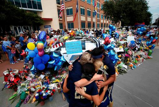 A softball team hugs after paying their respects at a makeshift memorial at Dallas Police Headquarters following the multiple police shootings in Dallas, Texas. Photo: Carlo Allegri/Reuters