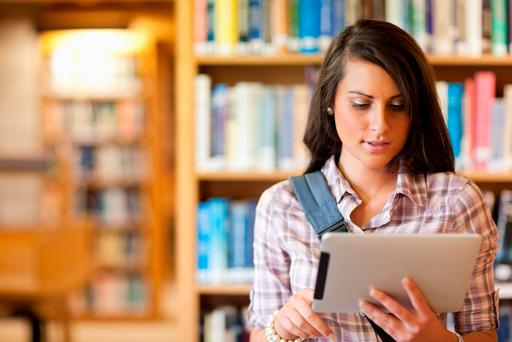 A student reads on a tablet in a college library (photo posed)