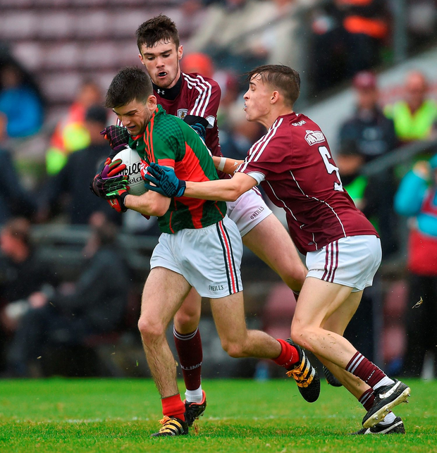 Oisin McLaughlin of Mayo is tackled by Sean Mulkerrin, left, and Adam Quirke of Galway. Photo by Ramsey Cardy/Sportsfile