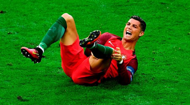 Cristiano Ronaldo reacts after suffering a knee injury during the first-half of last night's final following a tackle by Dimitri Payet. Photo: Getty Images