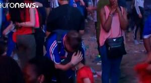 A young Portuguese fans consoles a distraught French supporter in Paris