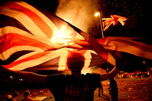 A boy holds a Union Jack flag in front of a bonfire burning in the Shankill Road area ahead of the Twelfth of July celebrations held by members of the Orange Order in Belfast, Northern Ireland, July 12, 2016. REUTERS/Clodagh Kilcoyne