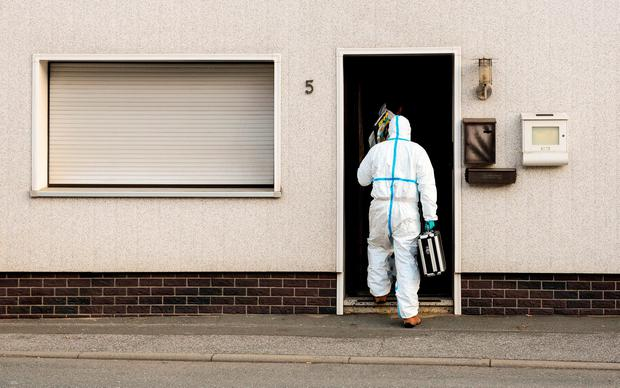 In this Nov. 13, 2015 file picture a police investigator in protective cloth enters a house in Wallenfels, southern Germany, where police found bodies of multiple babies. (Nicolas Armer/dpa via AP,file)