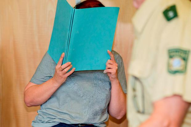 Defendant Andrea G. , who is accused of murder, covering her face with a folder, in the court room of the regional court in Coburg, Germany, Tuesday July 12, 2016. (Daniel Karmann/dpa via AP)