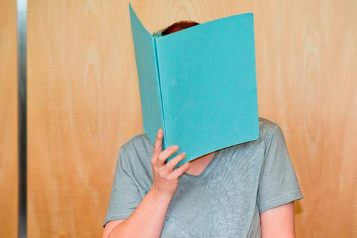 Defendant Andrea G, who is accused of murder, covering her face with a folder, in the court room of the regional court in Coburg, Germany, Tuesday July 12, 2016. (Daniel Karmann/dpa via AP)