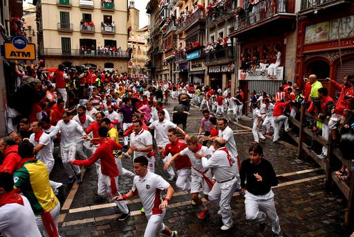 Revelers run around Nunez del Cubillo's fighting bulls on the Estafeta corner during the seventh running of the bulls at the San Fermin Festival, in Pamplona, northern Spain. (AP Photo/Alvaro Barrientos)