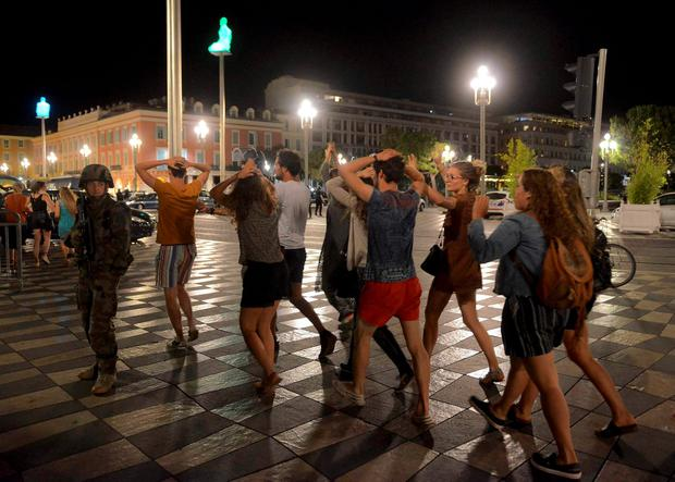 People cross the street with their hands on thier heads as a French soldier secures the area July 15, 2016 after at least 60 people were killed along the Promenade des Anglais in Nice, France, when a truck ran into a crowd celebrating the Bastille Day national holiday July 14. REUTERS/Jean-Pierre Amet