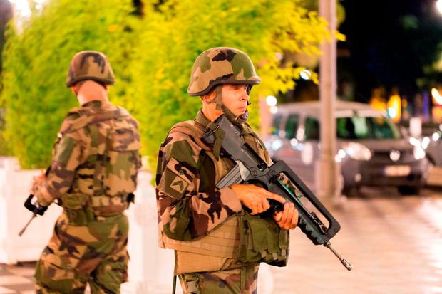 French soldiers stand guard by the sealed off area of an attack after a truck drove on to the sidewalk and plowed through a crowd of revelers who'd gathered to watch the fireworks in the French resort city of Nice, southern France. Photo: AP