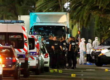 French police forces and forensic officers stand next to a truck that ran into a crowd celebrating the Bastille Day national holiday on the Promenade des Anglais killing at least 60 people in Nice, France. Photo: Reuters