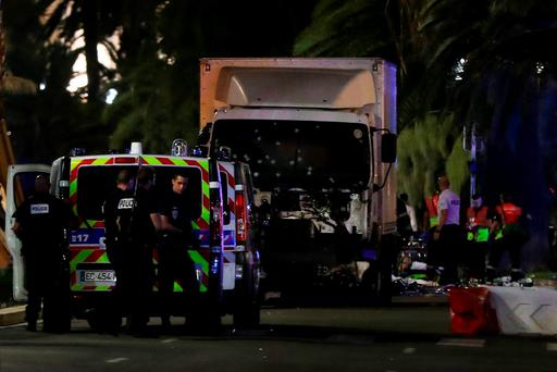 Police officers and rescued workers stand near a van that ploughed into a crowd leaving a fireworks display in the French Riviera town of Nice on July 14, 2016. AFP PHOTO / VALERY HACHEVALERY HACHE/AFP/Getty Images