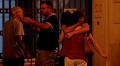 People comfort each other in the aftermath of the truck rampage in Nice. Below: Passers-by walk with their hands over their heads as soldiers stand guard after Nice went into lockdown. Photo: AFP/Getty