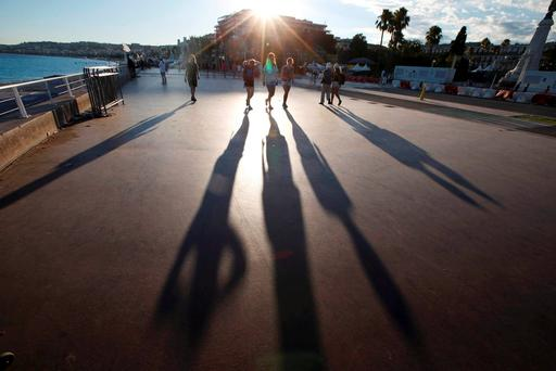 The sun casts long shadows as people walk on the Promenade des Anglais, in Nice. REUTERS/Eric Gaillard