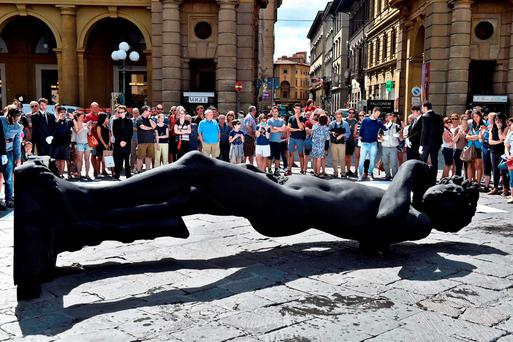 A life-size copy of renown Michelangelo Buonarroti's David is diplayed supine, as a tribute to the victims of the Nice attack, during a ceremony at the Repubblica square in Florence, Italy. Maurizio Degl'Innocenti/ANSA Via AP