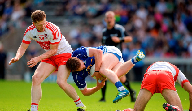 Jack Brady of Cavan in action against Enda Lynn, left, and Karl McKaigue of Derry