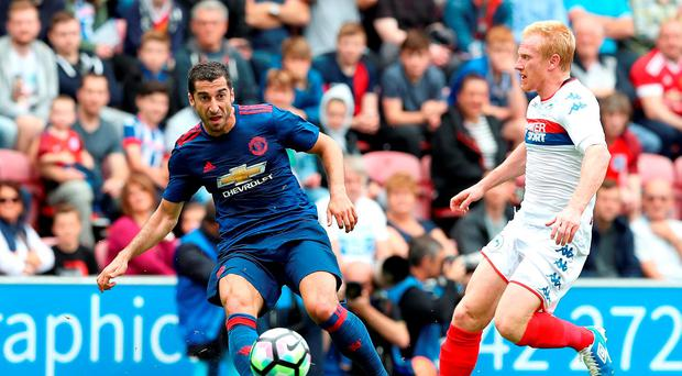 Manchester United's Henrikh Mkhitaryan (left) in action with Wigan Athletic's David Perkins