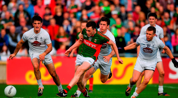 Diarmuid O'Connor of Mayo shoots to score his side's second goal despite the tackle of Emmet Bolton of Kildare