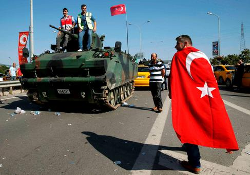 A man wrapped in a Turkish flag walks past a military vehicle in front of Sabiha Airport, in Istanbul, Turkey. REUTERS/Baz Ratner