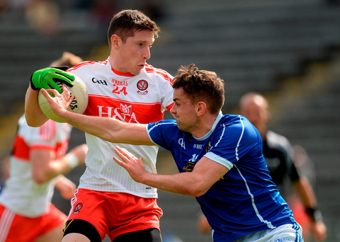 Derry's Emmett Bradley is resists a challenge from Niall Murray of Cavan. Photo by Brendan Moran/Sportsfile