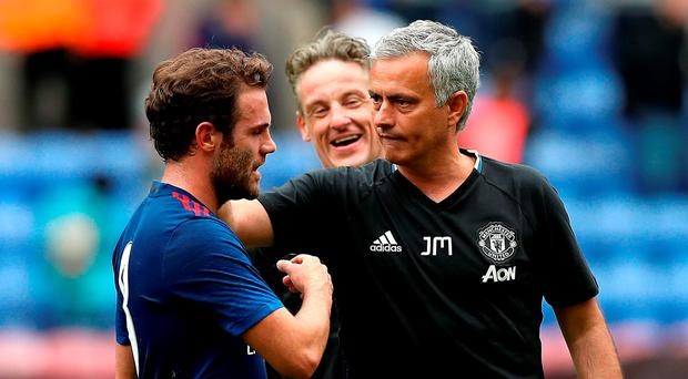 Manchester United's Juan Mata with manager Jose Mourinho after the friendly victory over Wigan. Photo: Martin Rickett