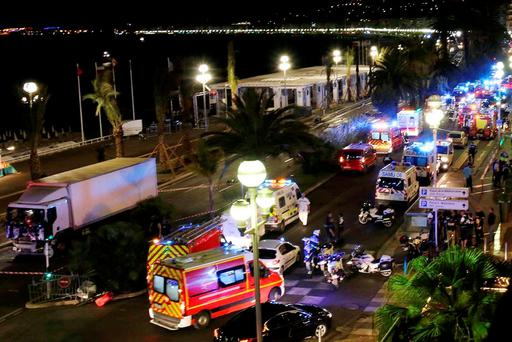 THE BASTILLE DAY MASSACRE: Emergency services vehicles work on the scene after a truck, left, plowed through Bastille Day revelers in the French resort city of Nice. Photo: AP