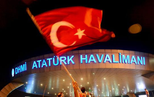 A man waves a Turkish flag in front of Ataturk Airport during an attempted coup in Istanbul. Turkish Airlines have since resumed flights from the airport. REUTERS/IHLAS News Agency