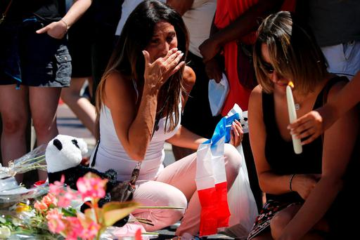 VIGIL: Women break down in tears reading poignant messages for victims of the Nice massacre. REUTERS/Pascal Rossignol