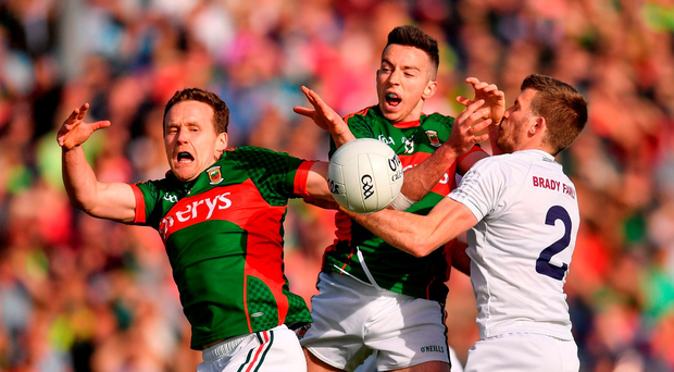 Andy Moran (left) and Evan Regan of Mayo battle for the ball with Kildare's Ciaran Fitzpatrick during last night's qualifier in MacHale Park. Photo: Stephen McCarthy