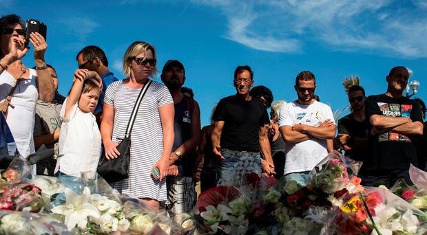 TERROR ATTACK: People stand near a makeshift memorial for the victims killed in the terrorist attack in Nice last week. Photo: AP