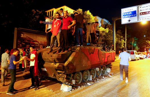 Supporters of Turkish President Tayyip Erdogan stand on an abandoned tank during a demonstration outside parliament building in Ankara, Turkey, July 16, 2016. REUTERS/Osman Orsal