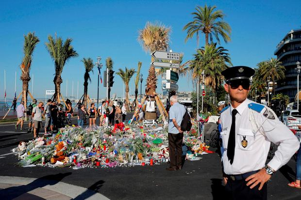 A police officer surveys people gathering around a floral tribute for the victims killed during a deadly attack, on the famed Boulevard des Anglais in Nice, southern France, Sunday, July 17, 2016. French authorities detained two more people Sunday in the investigation into the Bastille Day truck attack on the Mediterranean city of Nice that killed at least 84 people, as authorities try to determine whether the slain attacker was a committed religious extremist or just a very angry man. (AP Photo/Laurent Cipriani)