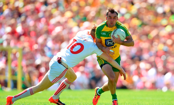 Karl Lacey of Donegal is tackled by Cathal McShane of Tyrone