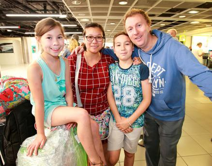 Conor Brennan from Castleknock pictured with his wife Tipparuit and their children Gemma [8] and Ollie [10] after they flew into Dublin Airport from Istanbul. Picture Credit: Frank Mc Grath