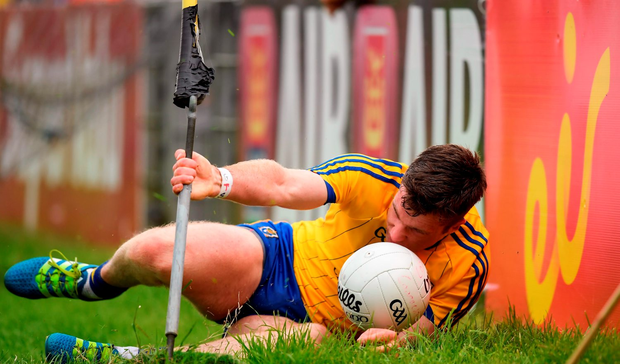 Cathal Cregg of Roscommon collides with the advertising boards