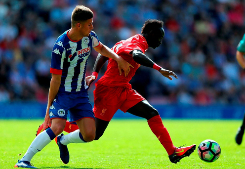 WIGAN, ENGLAND - JULY 17: Ryan Colclough of (L) Wigan Athletic challenges Sadio Mane of Liverpool during the Pre-Season Friendly. (Photo by Nigel Roddis/Getty Images)