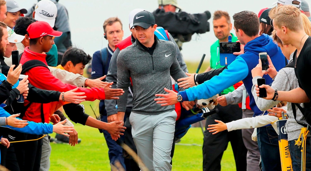 Rory McIlroy taps hands with spectators as he walks between holes during the final round on day four of the 145th Open Championship at Royal Troon. (Photo by Andrew Redington/Getty Images)