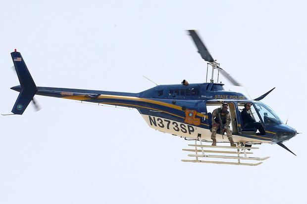 A law enforcement helicopter is seen near the scene where police officers were shot in Baton Rouge