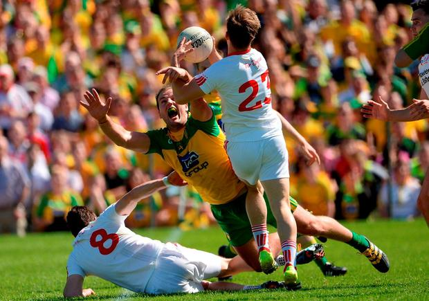 Michael Murphy is tackled and dispossessed by Tyrone's Kieran McGeary. Photo by Oliver McVeigh/Sportsfile