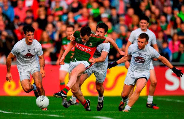 Diarmuid O'Connor scores Mayo's second goal despite the efforts of Emmet Bolton. Photo by Stephen McCarthy/Sportsfile