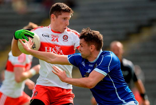 Derry's Emmett Bradley holds up the ball under pressure from Niall Murray. Photo by Brendan Moran/Sportsfile