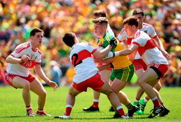Donegal's JD Boyle is swarmed by Derrymen Padraig McGrogan, Conor McCluskey and Eoghan Concannon. Photo by Oliver McVeigh/Sportsfile