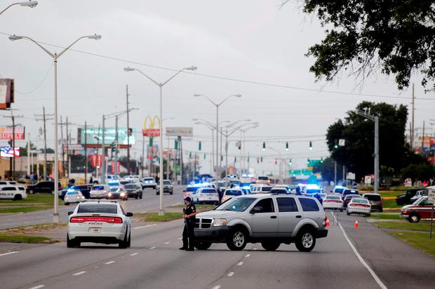 Police officers block off Airline Highway near the scene of a fatal shooting of police officers in Baton Rouge. REUTERS/Joe Penney