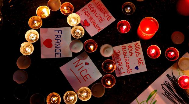 Burning candles, messages and a drawing pay tribute to victims of the truck attack along the Promenade des Anglais on Bastille Day that killed scores and injured as many in Nice. Photo: Pascal Rossignol/Reuters
