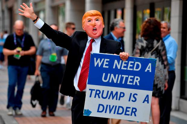 A man wearing a mask of Donald Trump walks through downtown ahead of the upcoming Republican National Convention. An estimated 50,000 people are expected in Cleveland, including hundreds of protesters. The four-day Republican National Convention kicks off on July 18. (Photo by Jeff J Mitchell/Getty Images)