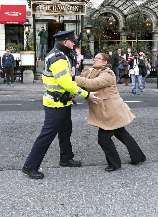 A garda tries to restrain a protester at the Mansion House