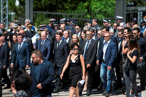 French Prime Minister Manuel Valls is flanked by security as he is jeered by the crowd