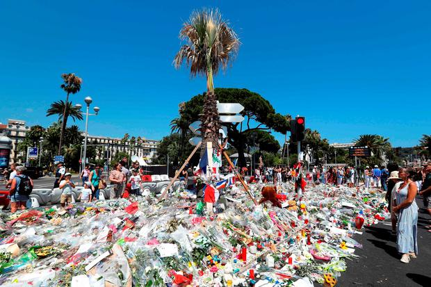 People gather near tributes placed at a makeshift memorial near the Promenade des Anglais in Nice. AFP/Getty Images