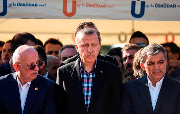 Turkey's President Recep Tayyip Erdogan (C) and former Turkish president Abdullah Gul (R) look on after attending the funeral of a victim of the coup attempt in Istanbul. AFP/Getty Images