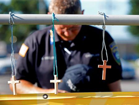Millville, N.J. police chaplain Robert Ossler prays at a makeshift memorial at the fatal shooting scene in Baton Rouge, where several law enforcement officers were killed on Sunday. (AP Photo/Gerald Herbert)
